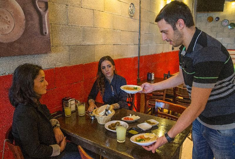 Kobi Tzafrir, serving diners on October 21, 2015, offers half off regular menu prices when Jewish and Arab patrons share tables at his Hummus Bar restaurant in the central Israeli town of Kfar Vitkin