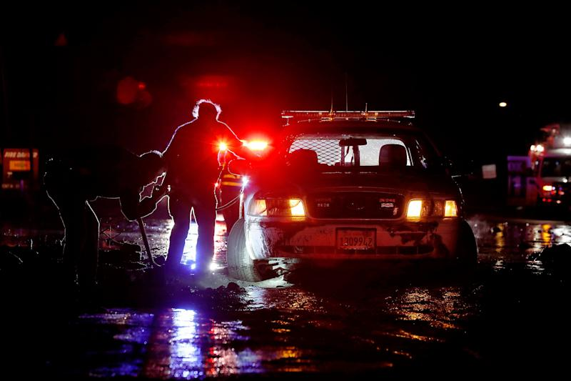 In this Saturday, Jan 5, 2019, photo sheriff's deputies work to free their patrol cruiser from mud covering a stretch of Pacific Coast Highway in Malibu, Calif. A winter storm unleashed mudslides in Southern California wildfire burn areas and trapped motorists on a major highway, and the northern part of the state is bracing for more wet weather. Saturday's deluge loosened hillsides in Malibu where a major fire burned last year, clogging the Pacific Coast Highway with mud and debris.