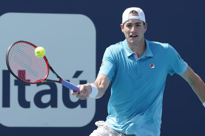 John Isner returns to Felix Auger-Aliassime of Canada during the Miami Open tennis tournament, Sunday, March 28, 2021, in Miami Gardens, Fla. (AP Photo/Marta Lavandier)