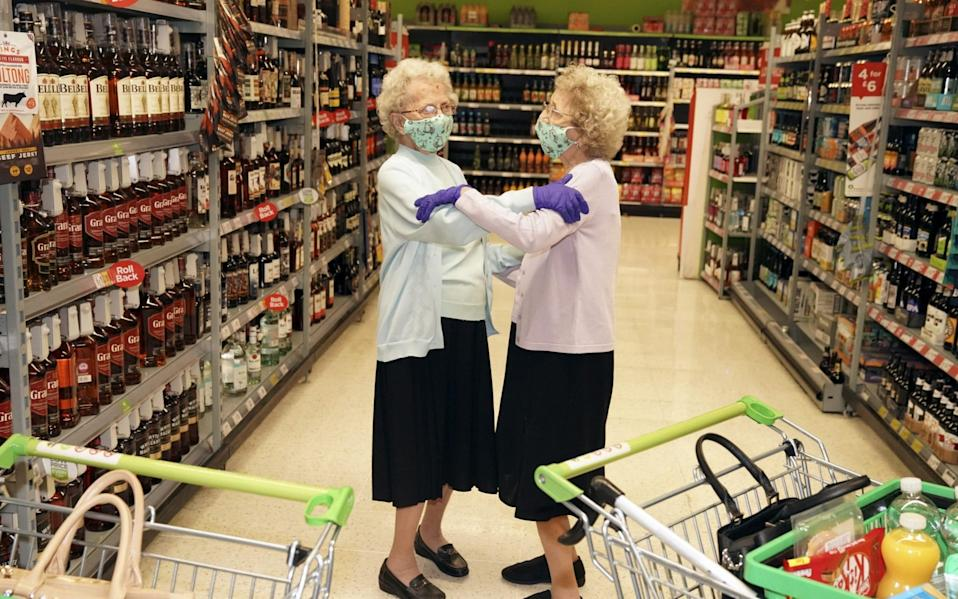 Twins Doris Hobday (L) and Lil Cox (R) pictured on a visit to Asda in August 2020 on what was their first trip out of the house for six months - Roland Leon/Daily Mirror