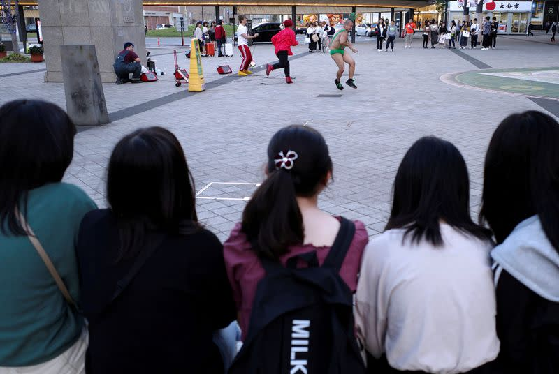 FILE PHOTO: Girls watch a music performance by street buskers in Oita