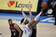 Oklahoma City Thunder guard Shai Gilgeous-Alexander (2) shoots between Chicago Bulls guard Garrett Temple (17) and forward Lauri Markkanen during overtime of an NBA basketball game Friday, Jan. 15, 2021, in Oklahoma City. (AP Photo/Sue Ogrocki)