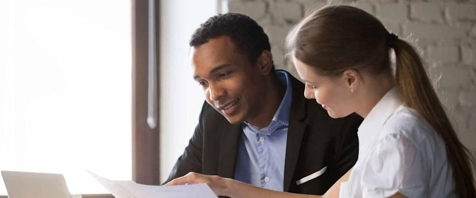 Woman showing man something on a piece of paper while they sit in an office.