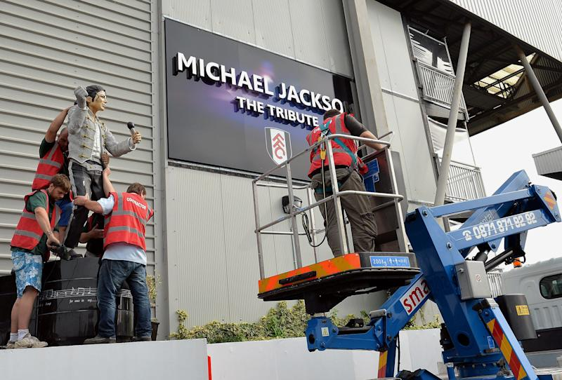 A group of stonemasons remove the statue of US performer Michael Jackson, that was erected by previous owner Mohammed al Fayed, on the north west corner of Fulham Football Club, West London, Wednesday Sept. 25, 2013. The controversial Michael Jackson statue which has stood outside Fulham's Craven Cottage ground for over two years was removed on Wednesday. Al Fayed sold the west London club to Shahid Khan in July and, after consulting with supporters, the American businessman decided to pull the 7ft 6in statue down. (AP Photo/PA, John Stillwell) UNITED KINGDOM OUT
