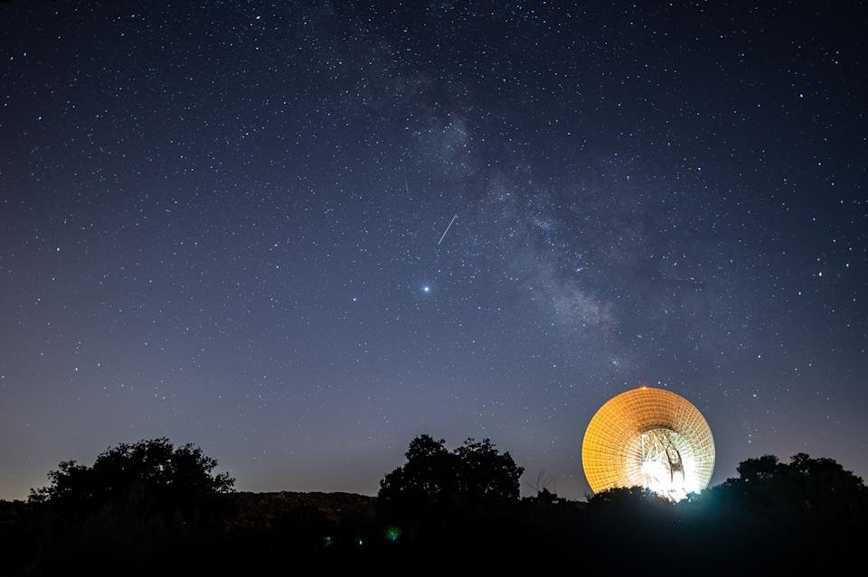 ROBLEDO DE CHAVELA, MADRID, SPAIN - 2020/08/19: A meteor crossing the night sky over the Milky way and a large antenna of the Madrid Deep Space Communications Complex of NASA and JPL, used for for tracking vehicles and spacecraft as well as for radioastronomy research. (Photo by Marcos del Mazo/LightRocket via Getty Images)