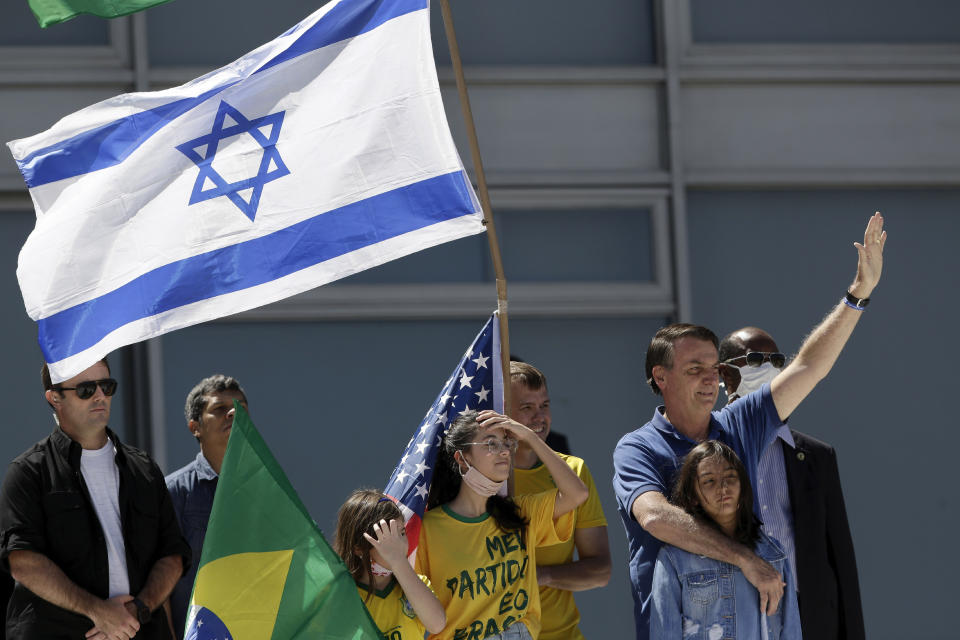 Brazil's President Jair Bolsonaro, right, embraces his daughter as supporters hold Israeli, American and Brazilian flags, during a protest against his former Minister of Justice Sergio Moro and the Supreme Court, in front of the Planalto presidential palace, in Brasilia, Brazil, Sunday, May 3, 2020. (AP Photo/Eraldo Peres)