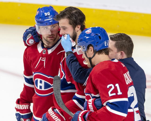 Montreal Canadiens center Phillip Danault (24) is helped off the ice by teammates Tomas Tatar (90) and Nick Cousins (21) after taking a puck to the face during second period NHL hockey action against the Arizona Coyotes Monday, Feb. 10, 2020 in Montreal. (Ryan Remiorz/The Canadian Press via AP)