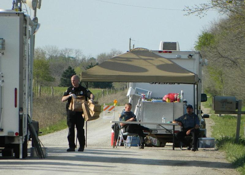 Investigators remove evidence from a home west of Ottawa, Kan., in Franklin County and carry it to a command trailer Tuesday May 7, 2013. The bodies of two adult men and one woman were found Monday on the farm. (AP Photo/The Topeka Capital Journal,Chris Neal )