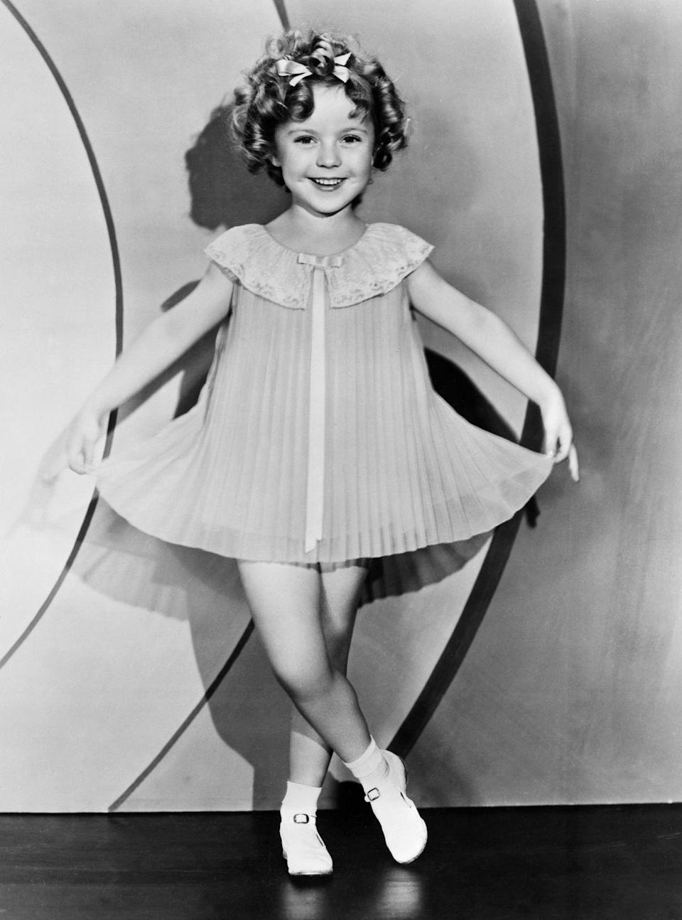 """<p>While the country was in the depths of the Great Depression, President Roosevelt referred to the child star as <a href=""""https://www.cnn.com/2014/02/11/showbiz/movies/shirley-temple-child-star-appreciation/index.html"""" rel=""""nofollow noopener"""" target=""""_blank"""" data-ylk=""""slk:Little Miss Miracle"""" class=""""link rapid-noclick-resp"""">Little Miss Miracle</a> and credited her with boosting the country's morale. By 1935, Shirley was the biggest film star in America. That year she released some of her most beloved films, including <em>Curly Top </em>to <em>The Littlest Rebel</em>, and worked with some of the biggest names in the business.<br></p>"""