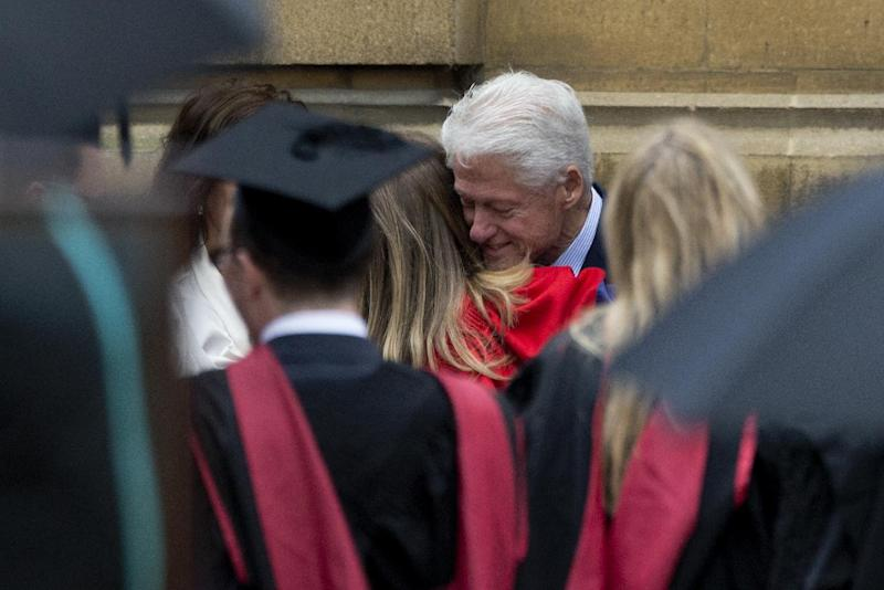 Former U.S. President Bill Clinton hugs his daughter Chelsea after attending her Oxford University graduation ceremony with his wife former Secretary of State Hillary Rodham Clinton held at the Sheldonian Theatre in Oxford, England, Saturday, May 10, 2014. Chelsea Clinton received her doctorate degree in international relations on Saturday from the prestigious British university. Her father was a Rhodes scholar at Oxford from 1968 to 1970. The graduation ceremony comes as her mother is considering a potential 2016 presidential campaign. (AP Photo/Matt Dunham)