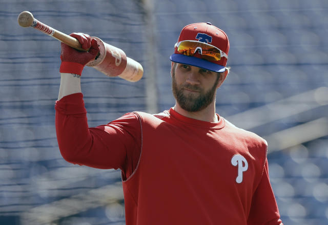 FILE - In this March 9, 2019 file photo Philadelphia Phillies' Bryce Harper waits his turn in the batting cage before a spring training baseball game against the Toronto Blue Jays in Clearwater, Fla. For the first time since 2011, the Washington Nationals will go through a season without any help from Bryce Harper. So it's rather likely this year will be viewed, at least in part, as a referendum on whether the Nationals should have figured out a way to keep the young slugger. (AP Photo/Chris O'Meara, file)