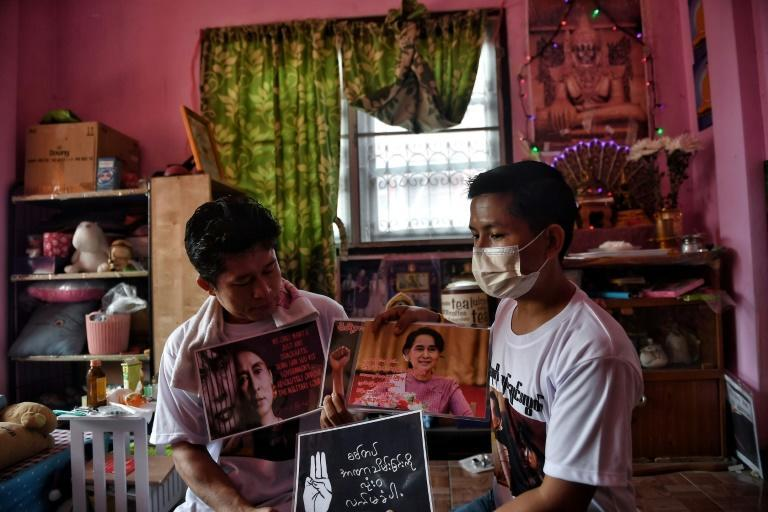 Myanmar shopkeeper and expat Kyaw Thu Ya (R) chooses signs to bring to a local protest against the military coup in his home country, at a house in the outskirts of Bangkok