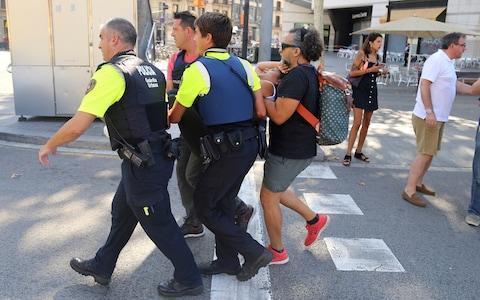 An injured person is carried in Barcelona, Spain - Credit: Oriol Duran/AP