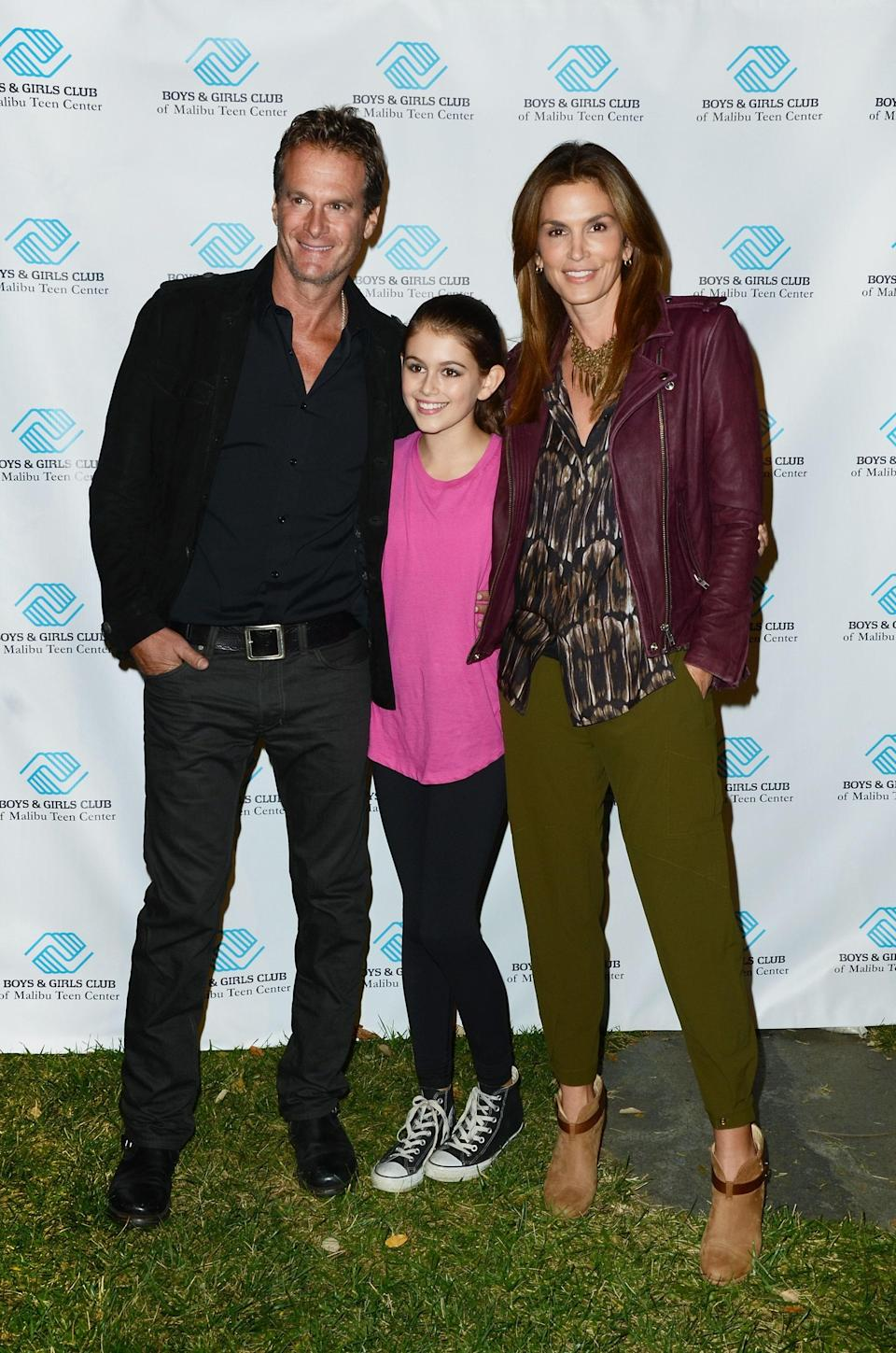 At a fundraiser with both her parents in 2013, Kaia kept it cool and casual in a fuschia top, black jeans, and her trusty, classic Converse high tops.
