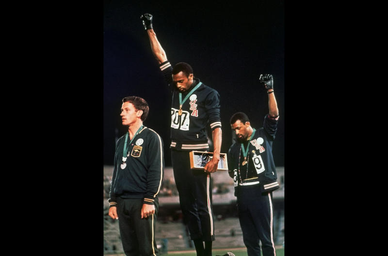 FILE - In this Oct. 16, 1968 file photo, U.S. athletes Tommie Smith, center, and John Carlos raise their gloved fists after Smith received the gold and Carlos the bronze for the 200 meter run at the Summer Olympic Games in Mexico City. Some athletes are criticizing the International Olympic Committee for prohibiting political protests on the medal podium. Olympic officials reminded athletes last week not to make political statements at the Tokyo Olympics. (AP Photo/File)