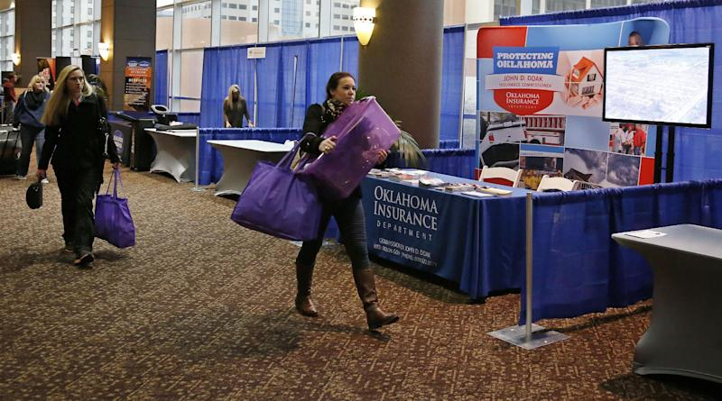 Katherine Lamers, of Dallas, Texas, with Housing Headquarters, carries supplies past the Oklahoma Insurance Department booth as vendors set up for the National Tornado Summit in Oklahoma City, Sunday, Feb. 9, 2014. About 85 percent of residents who were displaced by the large and deadly tornadoes that decimated Joplin, Mo., and Moore, Okla., have rebuilt or intend to, the communities' mayors said Monday. (AP Photo/Sue Ogrocki)