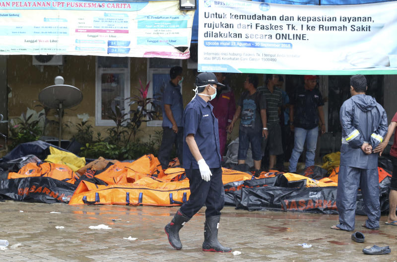 Wrapped bodies of tsunami victims are laid in Carita, Indonesia, Sunday, Dec. 23, 2018. The tsunami occurred after the eruption of a volcano around Indonesia's Sunda Strait during a busy holiday weekend, sending water crashing ashore and sweeping away hotels, hundreds of houses and people attending a beach concert. (AP Photo/Achmad Ibrahim)