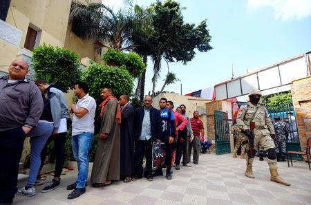 An Egyptian soldier stands guard as people wait in line to cast their votes during the second day of the referendum on draft constitutional amendments, at a polling station in Cairo, Egypt April 21, 2019. REUTERS/Amr Abdallah Dalsh