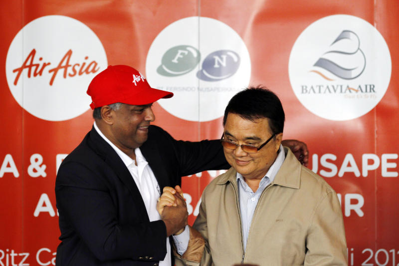 AirAsia Chief Executive Officer Tony Fernandez, left, greets Batavia Air President Director Yudiawan Tansari during a joint press conference in Jakarta, Indonesia, Thursday, July 26, 2012. Low-cost airline AirAsia said it is buying Indonesian budget carrier Batavia Air to expand in Southeast Asia's biggest economy. (AP Photo/Achmad Ibrahim)