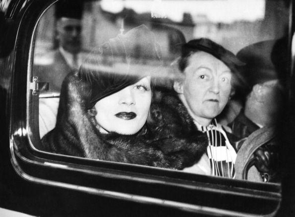 <p>Leaving Victoria station by car, Dietrich, who co-starred beside notable Hollywood actors like Charles Boyer, Fred MacMurray, and John Wayne, fixes a sultry gaze outside the window while wearing her signature fur, bold lip, and tilted hat.<br></p>