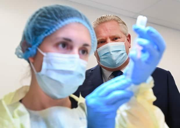 Ontario Premier Doug Ford watches a health care worker prepare a dose of the Pfizer-BioNTech COVID-19 vaccine at a UHN vaccine clinic in Toronto on January 7, 2021.