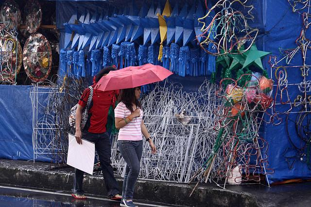 A woman passes by a lantern store in Makati City, south of Manila, rainy Tuesday afternoon. (Marlo Cueto/NPPA Images)