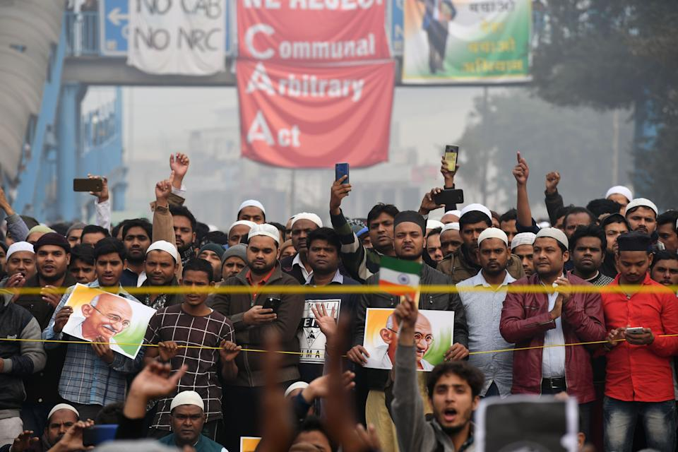 Protesters hold placards and shout slogans at a demonstration against Indias new citizenship law in New Delhi on December 20, 2019. - Fresh clashes between Indian police and demonstrators erupted on December 20 after more than a week of deadly unrest triggered by a citizenship law seen as anti-Muslim. (Photo by Prakash SINGH / AFP) (Photo by PRAKASH SINGH/AFP via Getty Images)