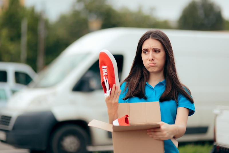 Young woman holds up a shoe above a box, looking disappointed.