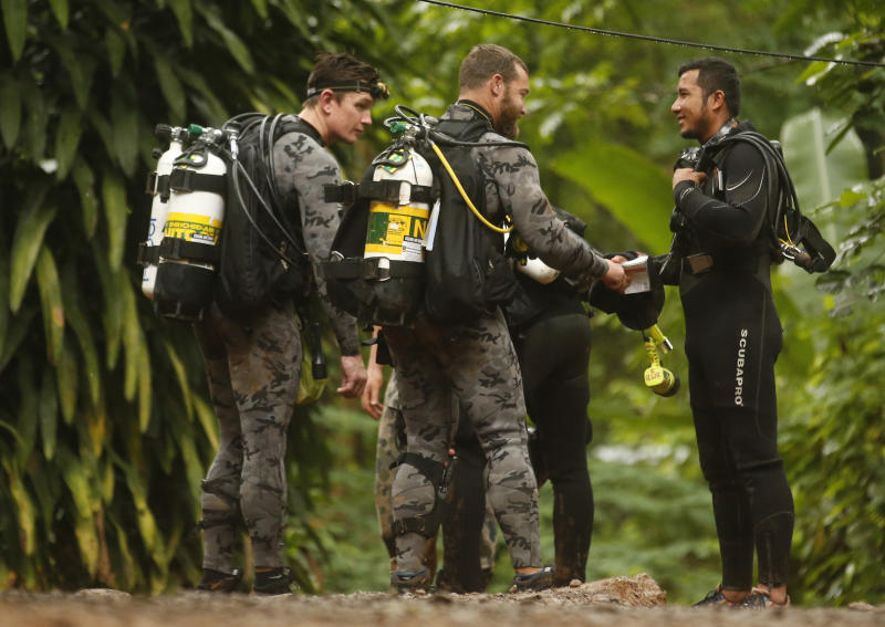 In this Tuesday, July 3, 2018, file photo, Australian Federal Police and Defense Force personnel talk with a Thai diver after the 12 boys and their soccer coach were found alive in a flooded cave in Mae Sai, Chiang Rai province, northern Thailand. (AP Photo/Sakchai Lalit)