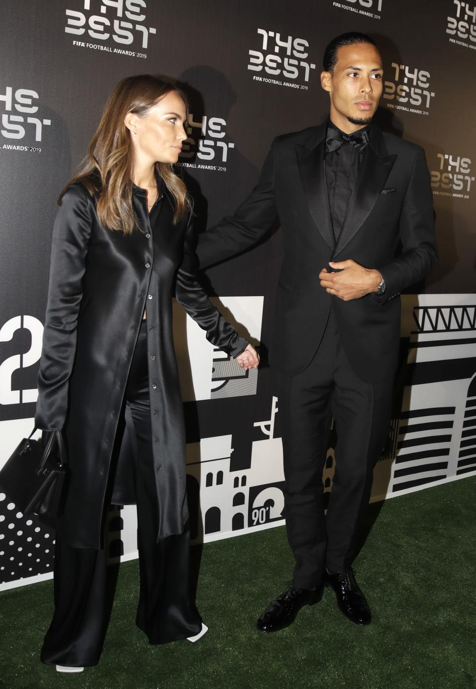 Netherlands defender Virgil van Dijk arrives with his partner Like Nooitgedagt to attend the Best FIFA soccer awards, in Milan's La Scala theater, northern Italy, Monday, Sept. 23, 2019. Virgil van Dijk is up against five-time winners Cristiano Ronaldo and Lionel Messi for the FIFA best player award and United States forward Megan Rapinoe is the favorite for the women's award. (AP Photo/Luca Bruno)