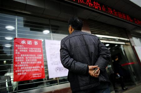 A man reads an announcement by the Rural Commercial Bank of Huanghai in one of the bank branches in Yancheng, Jiangsu province, March 26, 2014. REUTERS/Carlos Barria