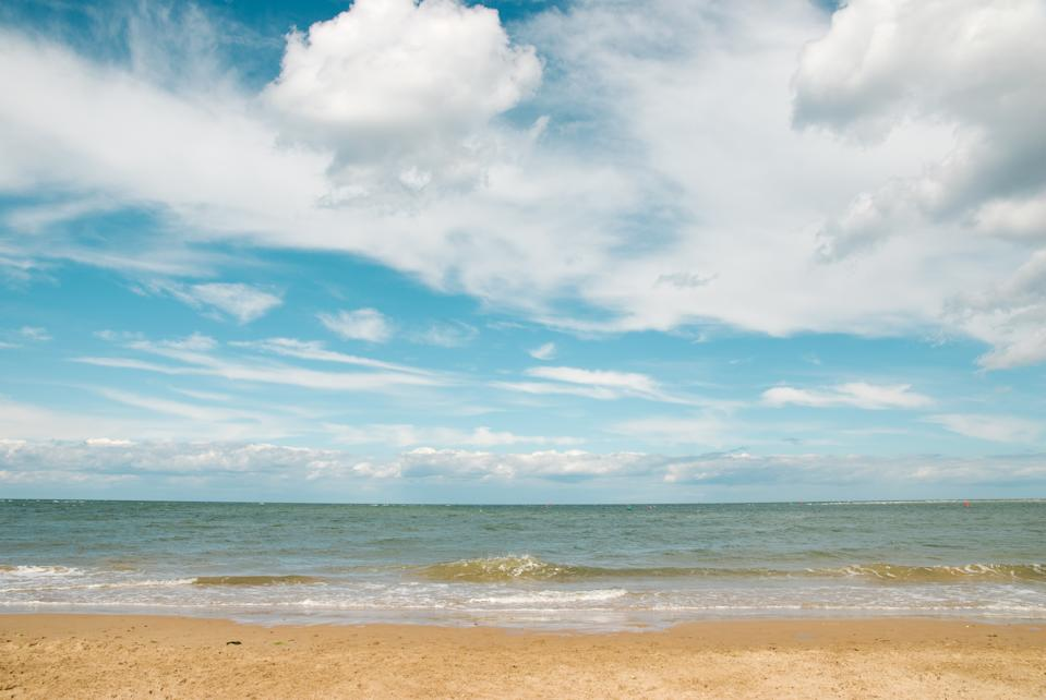 Beach and sea with a blue sky with white clouds background in summertime, Wells-Next-the-Sea, Norfolk, England, Uk.