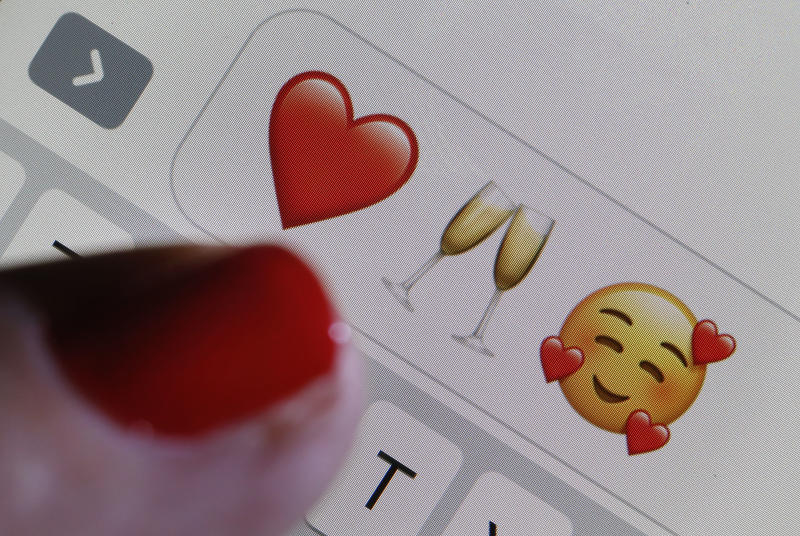 PARIS, FRANCE - FEBRUARY 14: In this photo illustration, an emoji or emoticon representing a heart, a glass of champagne and heart-shaped eyes are displayed on the screen of an iPhone on Valentine's Day on February 14, 2019 in Paris, France. Valentine's Day is known as the Lovers' Day and the celebration of love and romance in many parts of the world. (Photo by Chesnot/Getty Images)