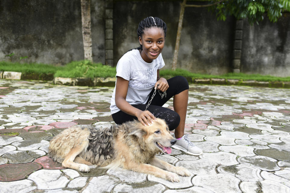 In this photo taken on Wednesday, Oct. 14, 2020, Dodeye Ewa, 16 year play with a dog outside her compound in Calabar, Nigeria. The third child is bothered by President Donald Trump's rhetoric and his policies toward international students, most recently one announced Friday that limits their stays in the U.S. to two or four years with uncertainty about whether their visas will be extended. (AP Photo/Daniel H Williams )