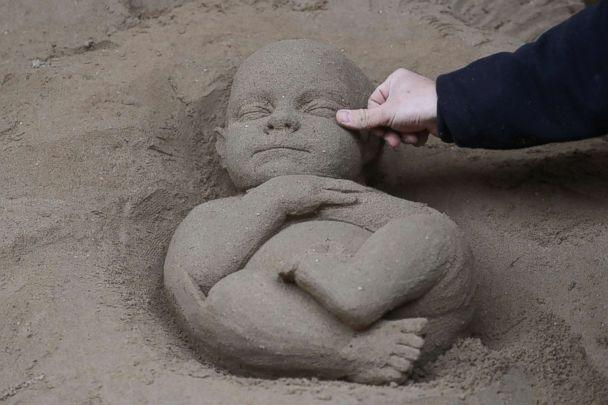 PHOTO: An artist works on a sand sculpture representing baby Jesus as a part of nativity scene in St. Peter's square at the Vatican, Dec. 6, 2018. (Alessandro Bianchi/Reuters)