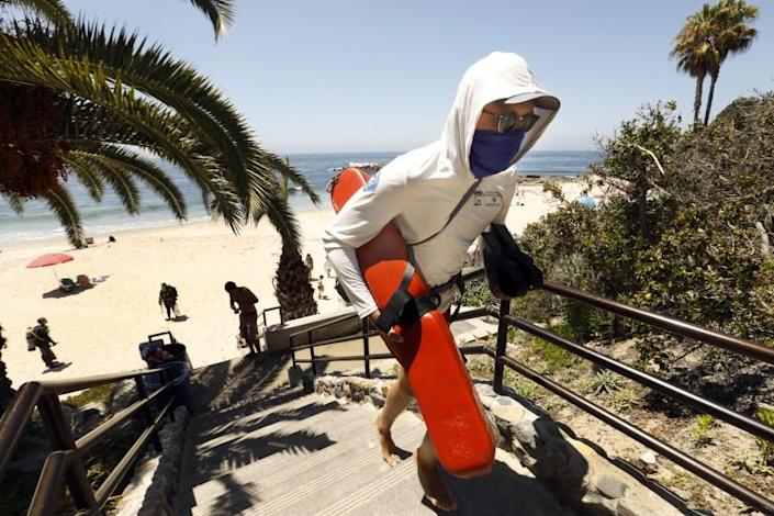 """A lifeguard wearing a face covering heads up the steps at Heisler Park in Laguna Beach. <span class=""""copyright"""">(Carolyn Cole / Los Angeles Times)</span>"""