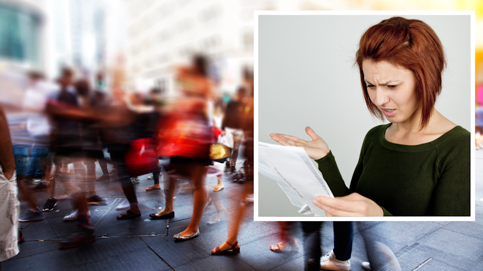 Blurred image of Australian pedestrians. Woman looking at bank statement, confused and angry.