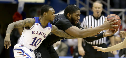 Kansas' Naadir Tharpe (10) tries to steal the ball away from Georgetown's Joshua Smith (24) during the first half of an NCAA college basketball game Saturday, Dec. 21, 2013, in Lawrence, Kan. (AP Photo/Charlie Riedel)