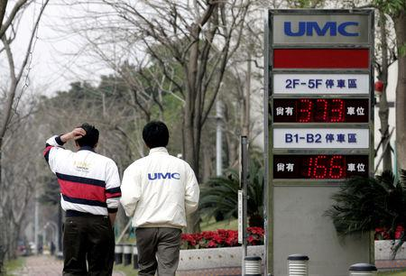 FILE PHOTO: Men walk past a signboard of chipmaker United Microelectronics Corp (UMC) in Hsinchu