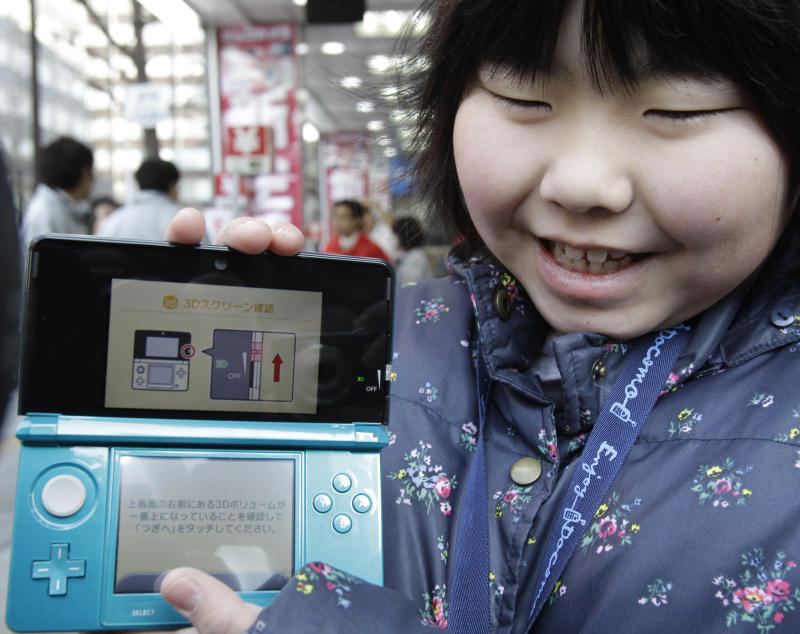 FILE - In this Feb. 26, 2011 file photo, Natsumi Miyasaka,9, shows off Nintendo's newest computer game console, Nintendo 3DS, at retail store Bic Camera in central Tokyo. Nintendo's annual profit dropped for the second straight year as sales of its gaming devices fell despite a price cut for the DS handheld, the Kyoto-based company behind the Super Mario franchise and the Wii console said Monday, April 25, 2011. (AP Photo/Koji Sasahara, File)