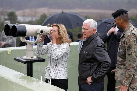 U.S. Vice President Mike Pence stands next to his daughter looking toward the north through a pair of binocular from an observation post inside the demilitarized zone separating the two Koreas, in Paju