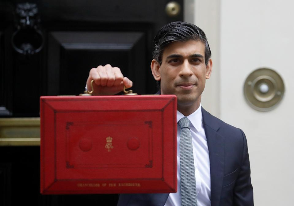 Rishi Sunak stands with his red briefcase in front of 11 Downing Street (AP)