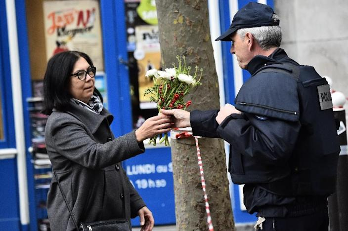 A woman asks a policeman to lay down flowers near a crime scene at the Rue de Charonne in Paris on November 14, 2015, following a series of coordinated attacks in and around the capital (AFP Photo/Loic Venance)