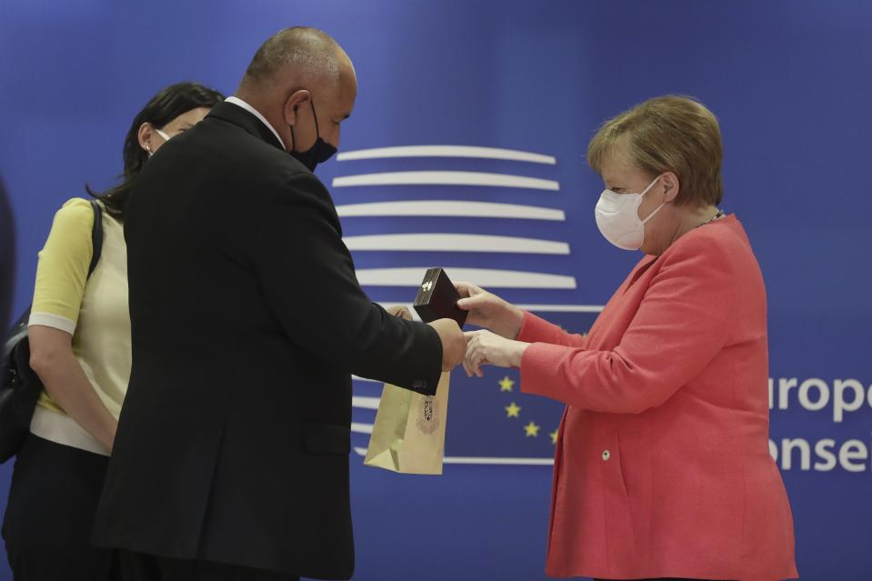 German Chancellor Angela Merkel, right, puts a gift in a bag as she speaks with Bulgaria's Prime Minister Boyko Borissov during a round table meeting at an EU summit in Brussels, Friday, July 17, 2020. Leaders from 27 European Union nations meet face-to-face on Friday for the first time since February, despite the dangers of the coronavirus pandemic, to assess an overall budget and recovery package spread over seven years estimated at some 1.75 trillion to 1.85 trillion euros. (Stephanie Lecocq, Pool Photo via AP)