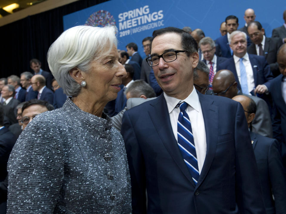International Monetary Fund (IMF) Managing Director Christine Lagarde speaks with Treasury Secretary Steven Mnuchin during the International Monetary Fund IMF Governors group photo at the World Bank/IMF Spring Meetings in Washington, Saturday, April 13, 2019. (AP Photo/Jose Luis Magana)