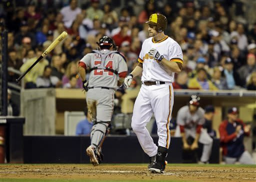 San Diego Padres' Chase Headley sends his b at flying as Washington Nationals catcher Kurt Suzuki heads toward the dugout after Headly struck out with a runner in scoring position to end the fifth inning of a baseball game in San Diego, Friday, May 17, 2013. (AP Photo/Lenny Ignelzi)