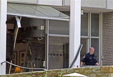 A Baltimore county police officer walks out the broken door at the entrance of the WMAR-TV station, after a possibly armed man crashed a truck into the Maryland television news station and barricaded himself inside the building, in Towson, Maryland May 13, 2014. REUTERS/Jose Magana