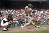 San Diego Padres' Fernando Tatis Jr., right, hits a home run in front of San Francisco Giants catcher Curt Casali during the third inning of a baseball game in San Francisco, Thursday, Sept. 16, 2021. (AP Photo/Jeff Chiu)