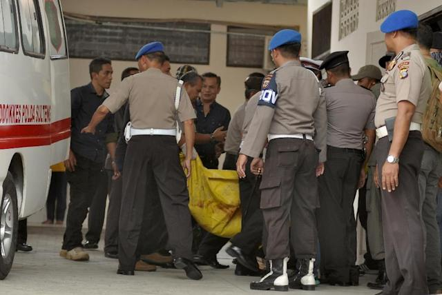 Police carry a body bag at a local hospital in Palu, Indonesia's Sulawesi province, on July 19, 2016, after a firefight between suspected Muslim extremists and security forces in the village of Tambarana (AFP Photo/Olagondronk)
