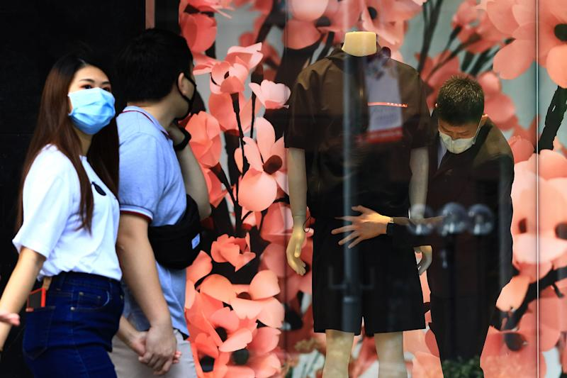 A worker wearing a protective mask prepares a window display at a Prada boutique at Orchard Road on 20 June, 2020, in Singapore. (PHOTO: Getty Images)